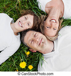 happy family lying on green grass - top view of a happy...