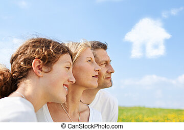 family dreaming of new house - family standing in nature and...