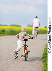father and son riding bikes - rear view of father and son...