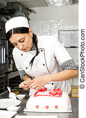 Pastry Cake Decorating - pastry chef decorates a cake in a...