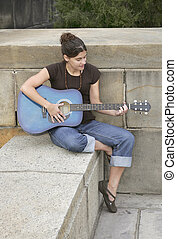 woman playing guitar - one brunette attractive woman playing...