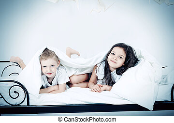 night dreams - Cute kids lying together on the bed under the...