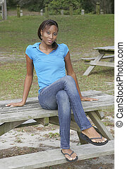 woman on picnic table - one African American young woman...