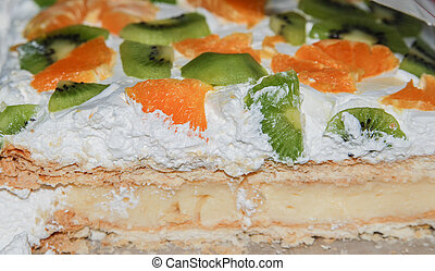 Fruits cake view in section with orange, kiwi, and a lotof...