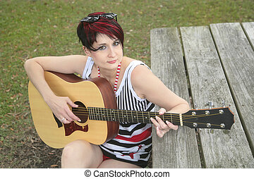 woman playing guitar - one young woman playing guitar on a...