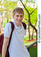 Young, smiling college male student outside