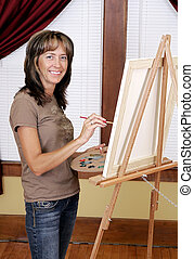 smiling painter - a woman smiling while painting a picture...