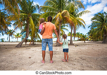 Rear view of father with two kids walking at beach