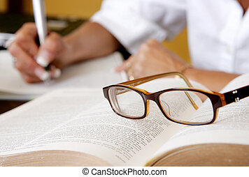researcher writing with glasses - a woman\\\'s hand writing...