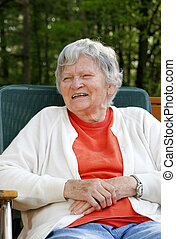 elderly woman laughing outdoors