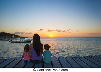 Mom and daughters silhouette in the sunset on the bridge