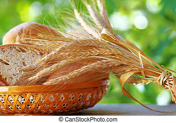 Basket of  bread , wheat spikes on table .
