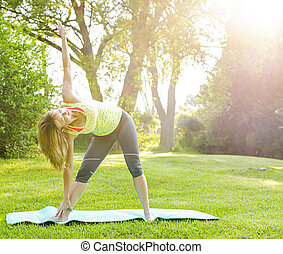 Woman in yoga triangle pose - Female fitness instructor...