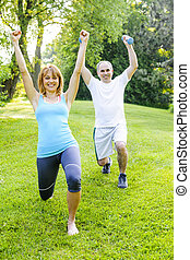 Personal trainer with client exercising outdoors - Female...