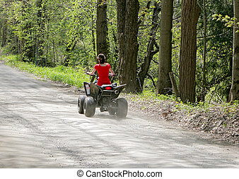 woman in red on four wheeler - young adult female riding a 4...