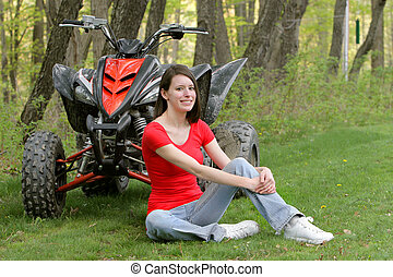 woman sitting with ATV - young adult female sitting beside a...