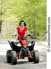 woman in red on four wheeler - oncoming close up young adult...