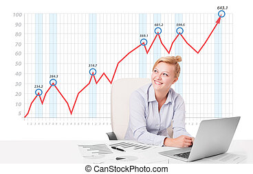 Beautiful young businesswoman calculating stock market with...