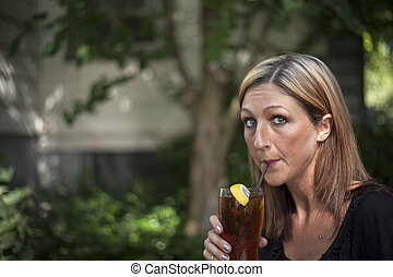 Blonde Woman with Beautiful Blue Eyes and Glass of Iced Tea...