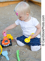 Toddler plays with toys on sandbox