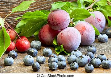 Blueberry, plums and wild apples on a wooden background