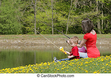 mother and son fishing - a woman and her young boy child go...
