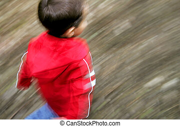 boy running with motion blur - a young male running with...