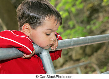 boy looking over a railing at a bridge - a young male child...