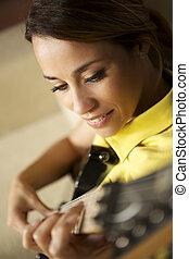 woman playing and training with electric guitar at home -...