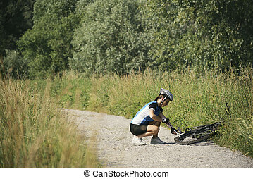 young woman training on mountain bike and cycling in park -...