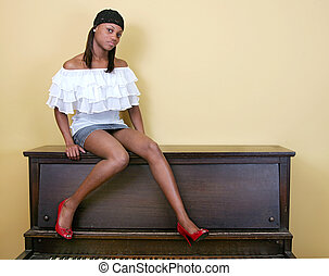 hot woman sitting on a piano - a sexy beautiful African...