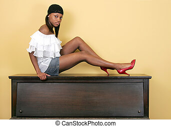 sexy woman sitting on a piano - a sexy beautiful African...