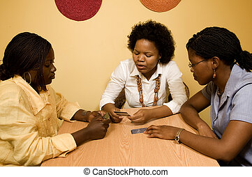 Discuss finances - 3 African women sitting at a table in...