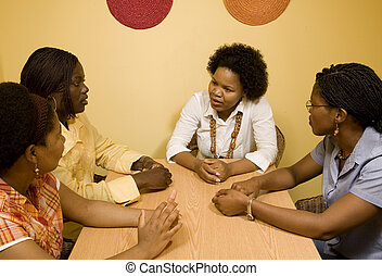 Meeting between peers - African women sitting at a table in...