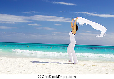 happy woman with white sarong on the beach