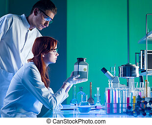 scientists with toxic waste container - close-up of two...