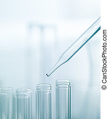 Pipette with a group of medical tubes - A pipette above two...