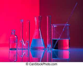 A set of glass labware on table - Red background with...