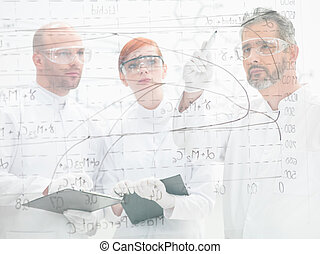 Scientists discussing a diagram - Three scientists standing...