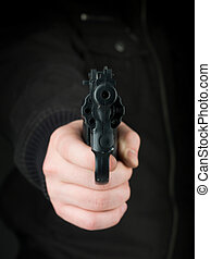 threat at gunpoint - closeup of the hand of a person dressed...
