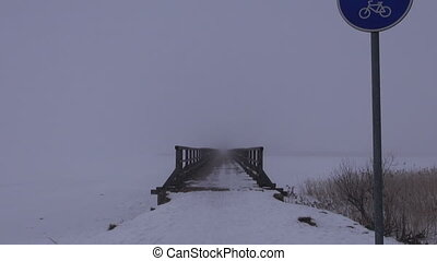 wooden bridge in dark winter mist