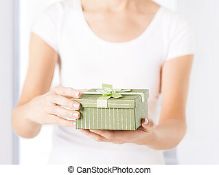 woman hands with gift box - close up of woman hands holding...