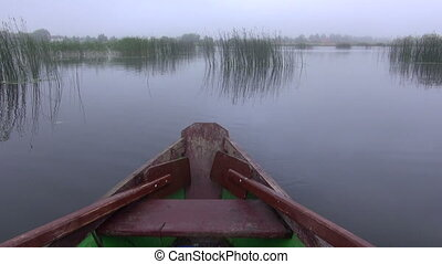 wooden boat with oars on lake