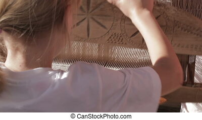 Girl working with traditional loom