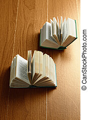 Two open books on a wooden surface