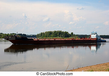 barge - floating on the river barge on the background of...