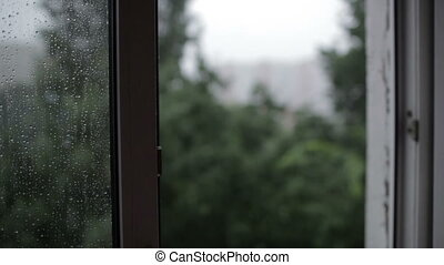 Heavy rain. Focus pulling from window to the building.