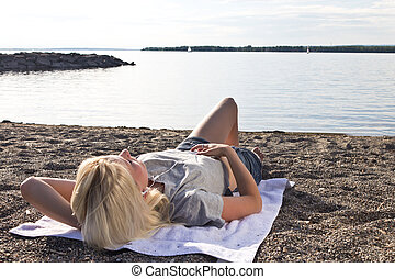 Young woman on the beach listening to music