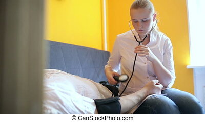 Doctor measures the blood pressure at home