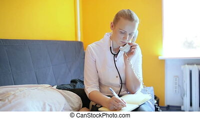 Female Doctor is speaking on the phone and making notes -...